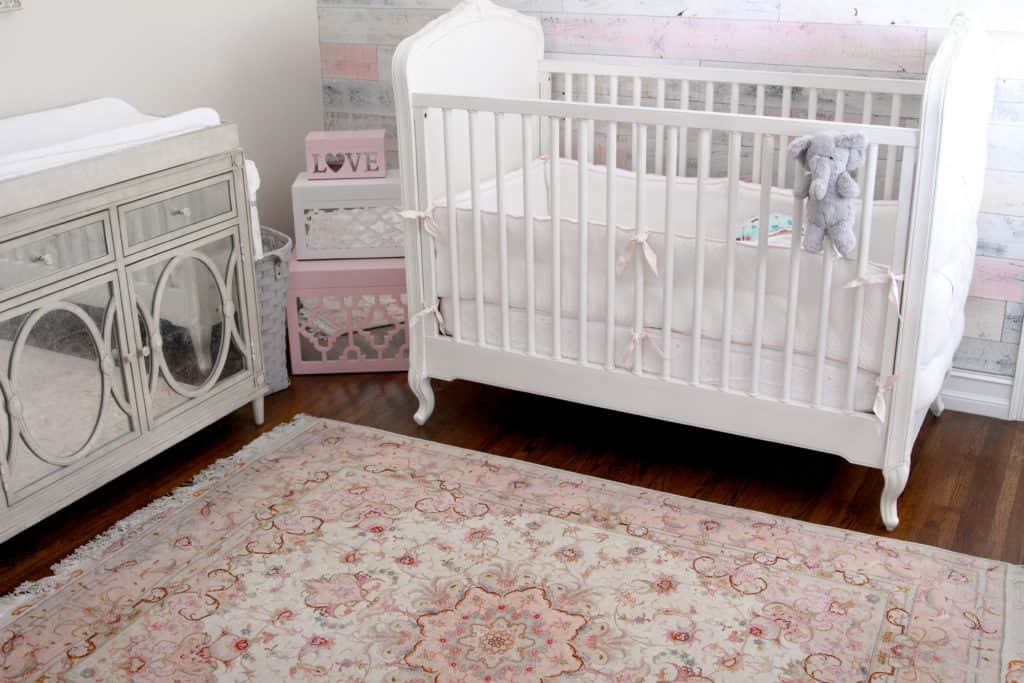 Pink and White Rustic Chic Nursery Decor - including an antique rug, Restoration Hardware Baby crib and dress, and a wood wall