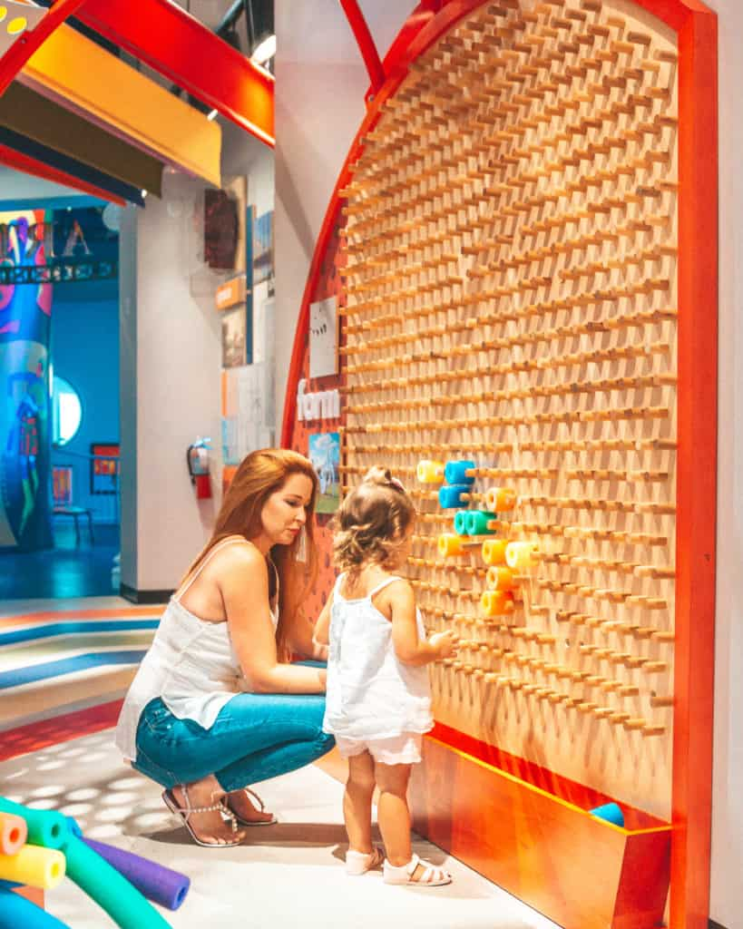 Inside the Miami Children's Museum in Miami Beach. The Art Studio has this peg wall with colorful rings that my daughter loved. Such a great idea to replicate for your home.