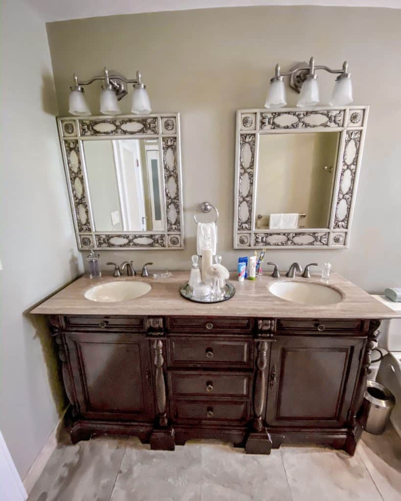 Before our farmhouse chic bathroom renovation: We had a dark wood vanity with sage green walls and silver mirrors.