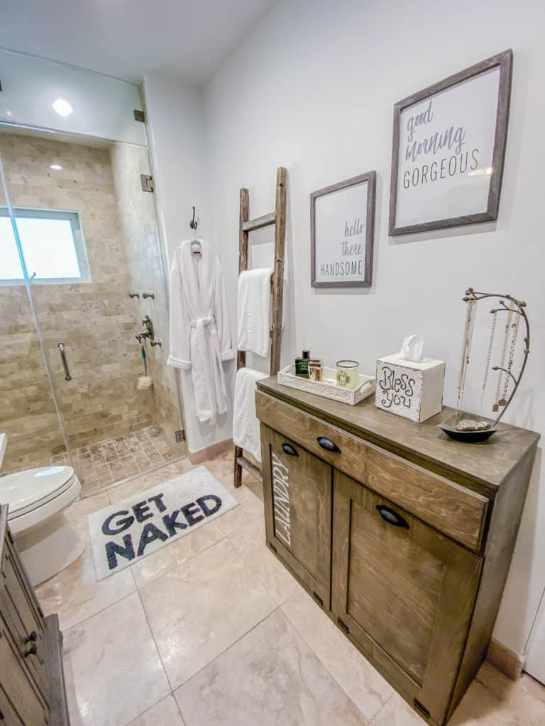 Farmhouse Stenciled Tilt Out Hamper, Good Morning Gorgeous / Hello There Handsome Frames, Get Naked Rug & a distressed ladder for our towels - bathroom renovation update  | Farmhouse Chic Bathroom Makeover | Bathroom Renovation | Update | Remodel | #bathroomremodel #bathroommakeover #bathroomrenovation #farmhouse #farmhousebathroom #bathroomreno #modernfarmhouse