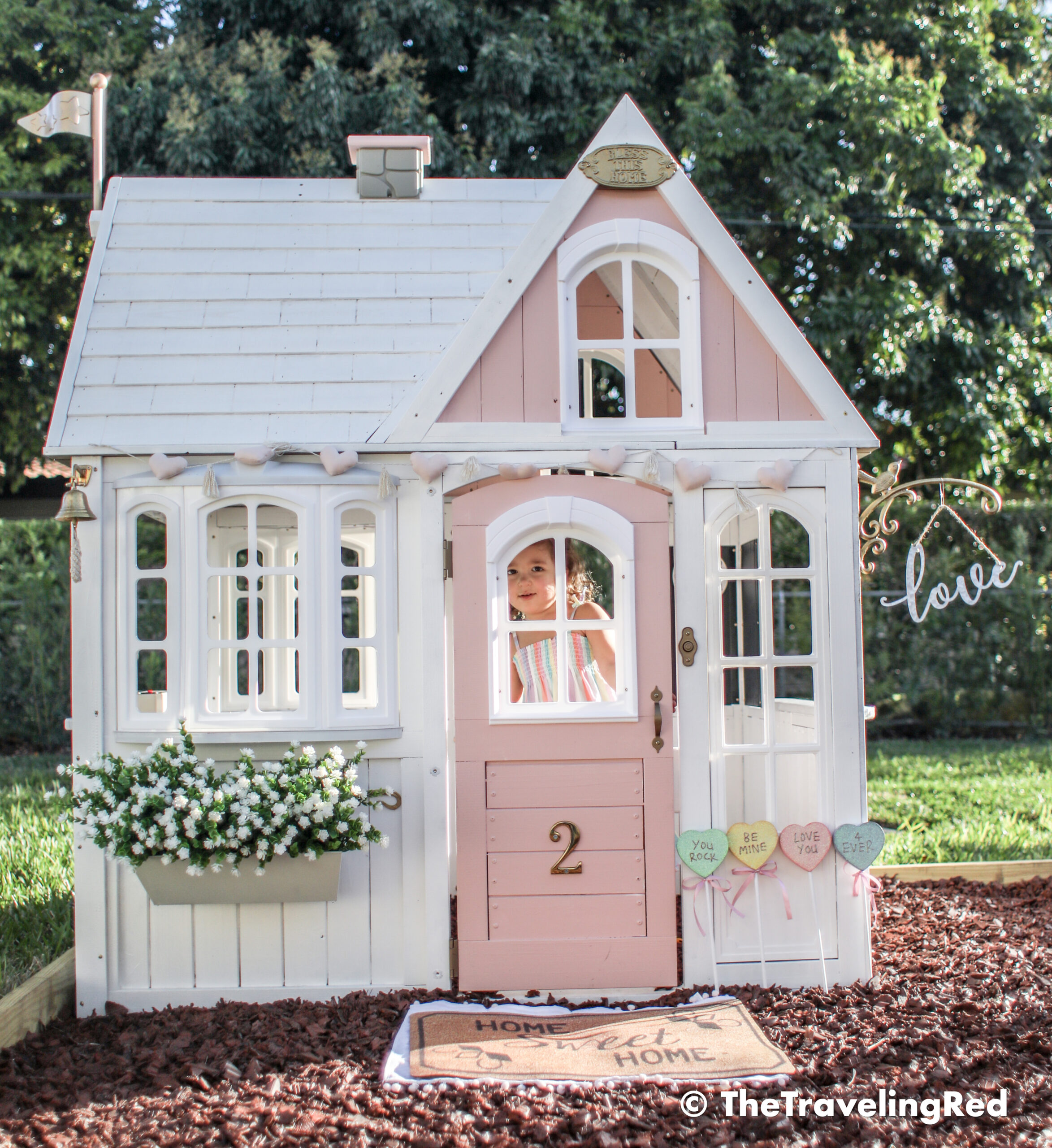 Valentine's Day Playhouse Decor - Kid's outdoor playhouse makeover decorated for Valentines Day using garland, candies and a little sign. Pink & white outdoor playhouse #valentinesday #valentinesdaydecor #homedecor #playhouse #playhousemakeover #valentinesdayhomedecor