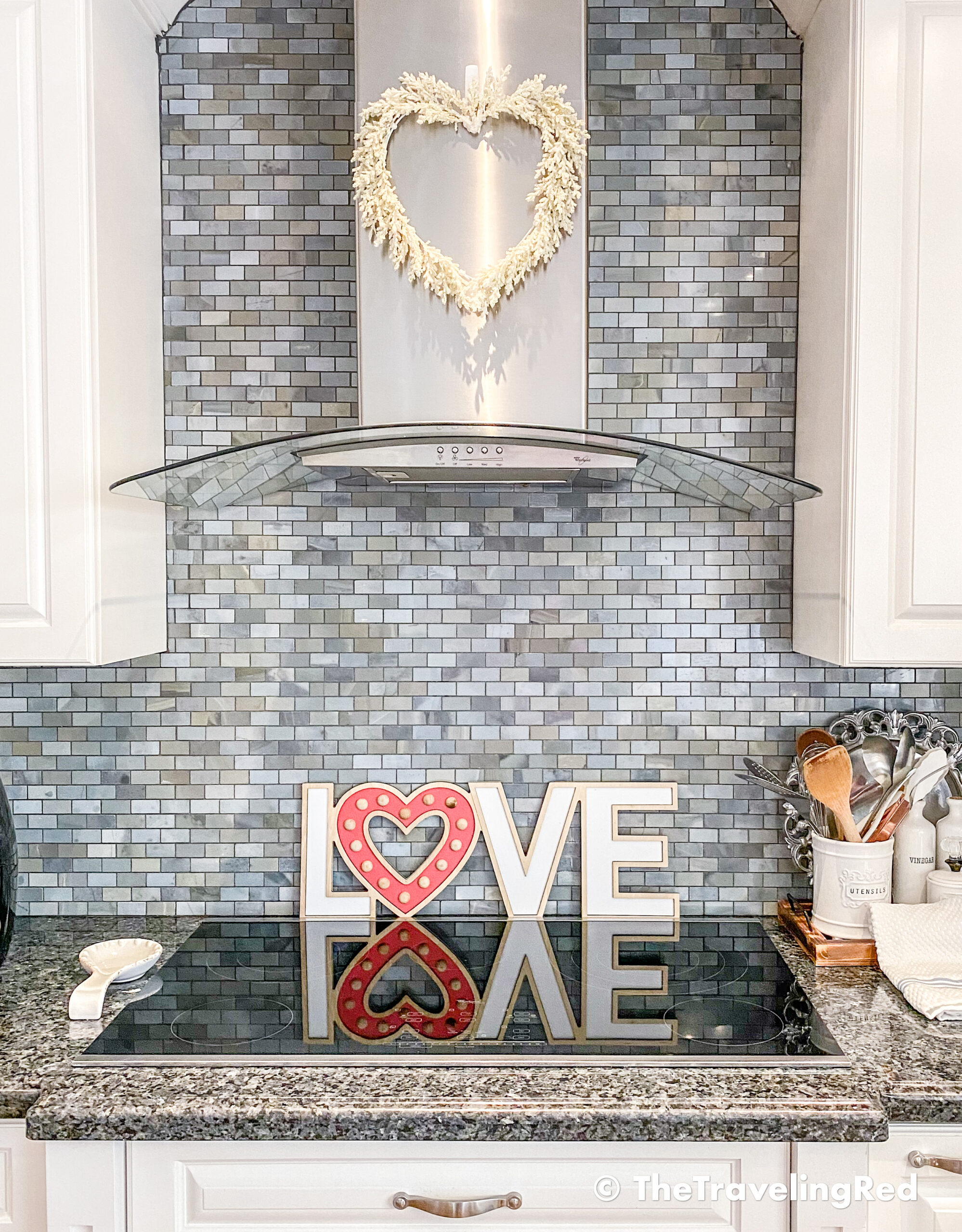 Valentine's Day Home Decor - Kitchen styling using a simple wh8ite heart wreath on my hood and a wood love sign behind the range - #valentinesday #valentinesdaydecor #homedecor #kitchendecor #valentinesdayhomedecor