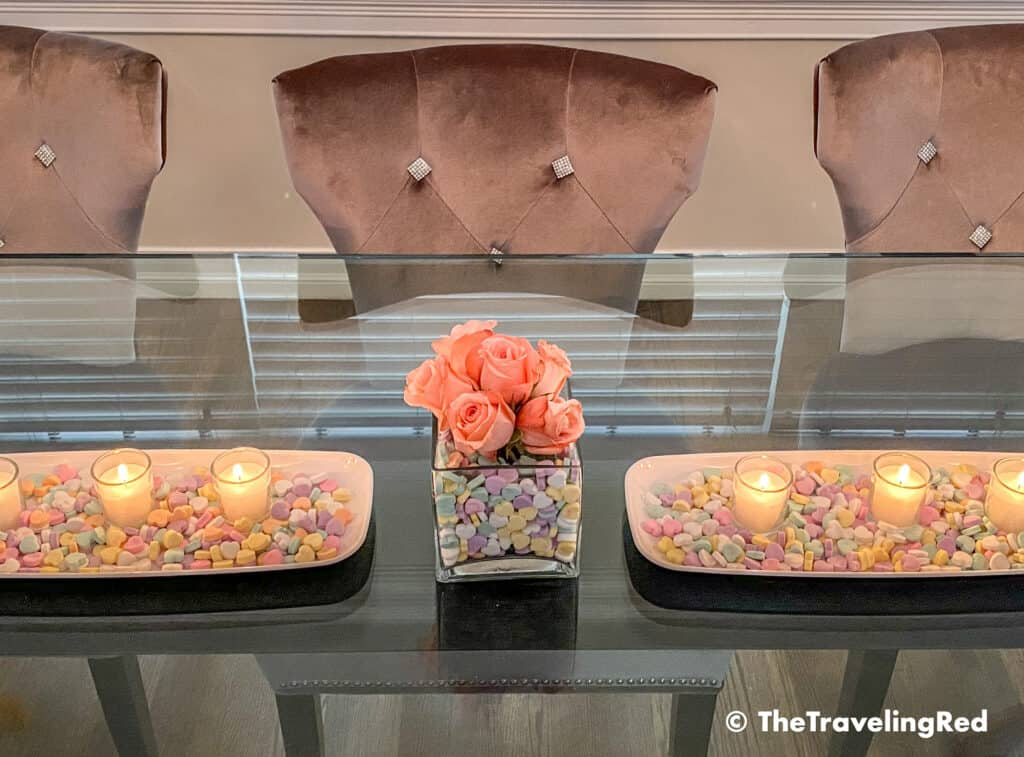 Valentine's Day Home Decor Dining Room Table Decor for a Valentines Day party using plastic trays, glass vases, sweetheart candies, votive candles & fresh roses - #valentinesday #valentinesdaydecor #homedecor #tabledecor #valentinesdayhomedecor