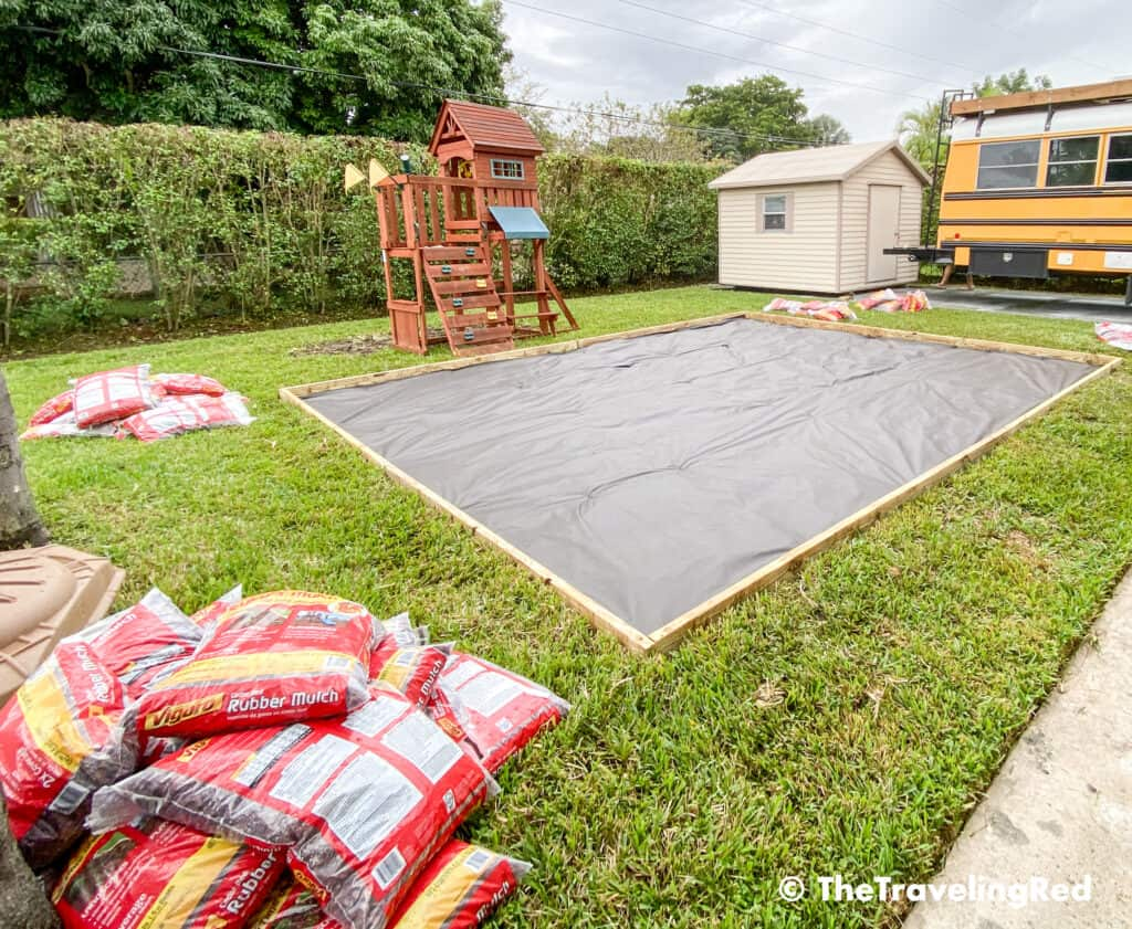 How to build a custom backyard playground with rubber mulch. Step 4 is to add a protective landscape barrier sheet to keep the weeds from growing out into the play area. This space will fit our swingset, playhouse, sandbox or any other outdoor toys you plan to include. Perfect little outdoor play space for your kids to enjoy playing outside.