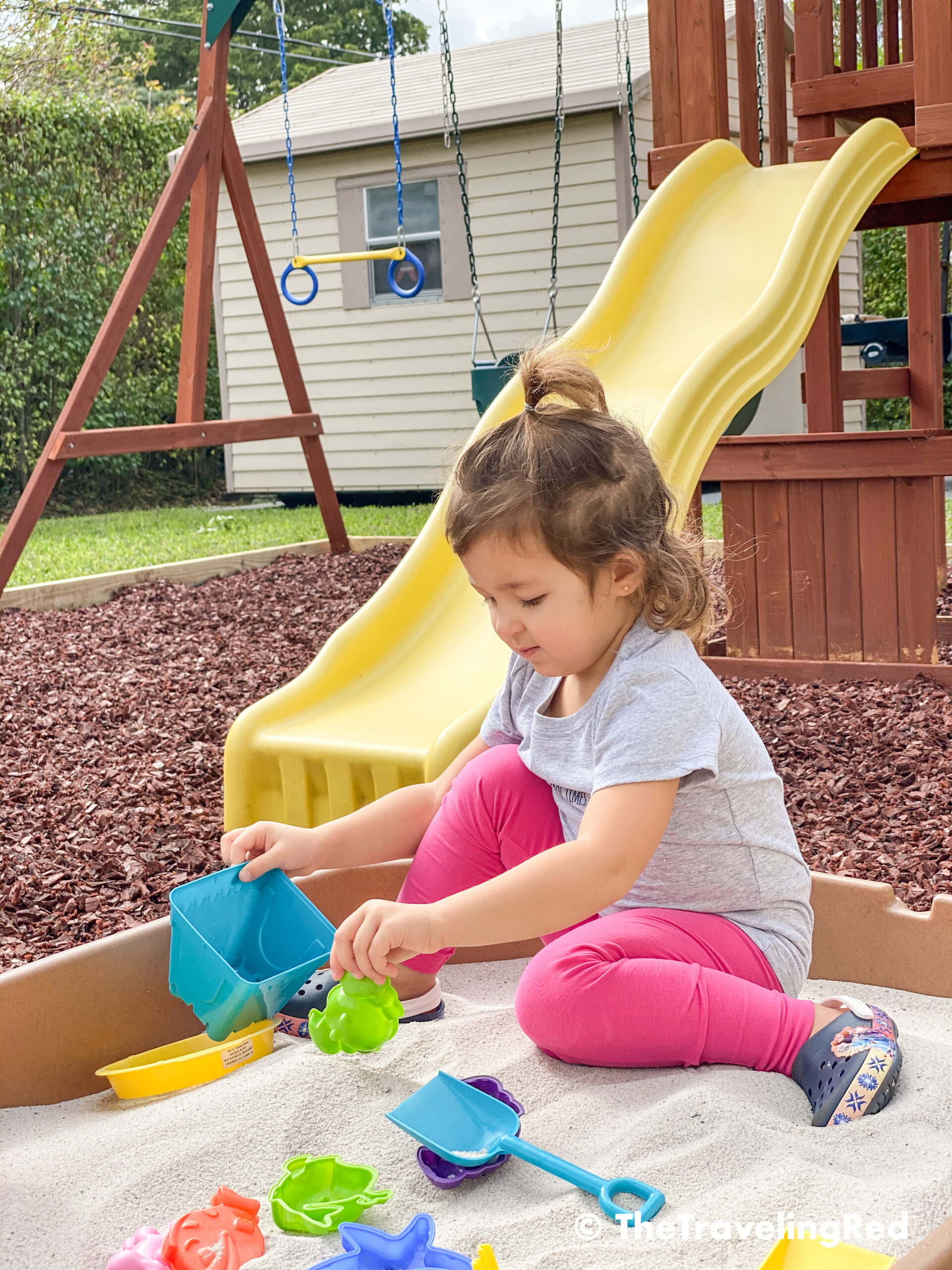 How we built a custom backyard playground with rubber mulch for our swingset, playhouse and sand box. Our sandbox is filled with beach toys and she loves playing in it. This outdoor playground is perfect little outdoor play space for your kids and it's soft on the feet.