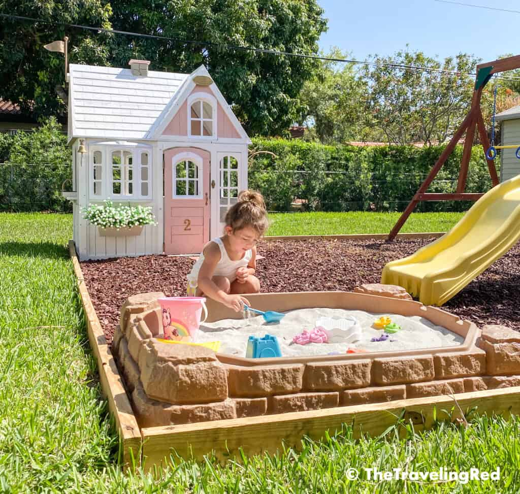How we built a custom backyard playground with rubber mulch for our swingset, playhouse and sand box. Perfect little outdoor play space for your kids and it's soft on the feet.