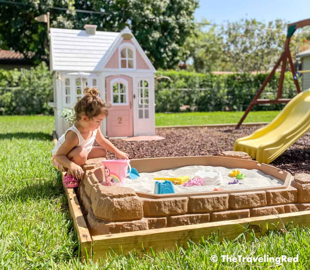 How we built a custom backyard playground with rubber mulch for our swingset, playhouse and sand box. Our sandbox is filled with beach toys and she loves playing in it for hours on end. This outdoor playground is perfect little outdoor play space for your kids and it's soft on the feet.