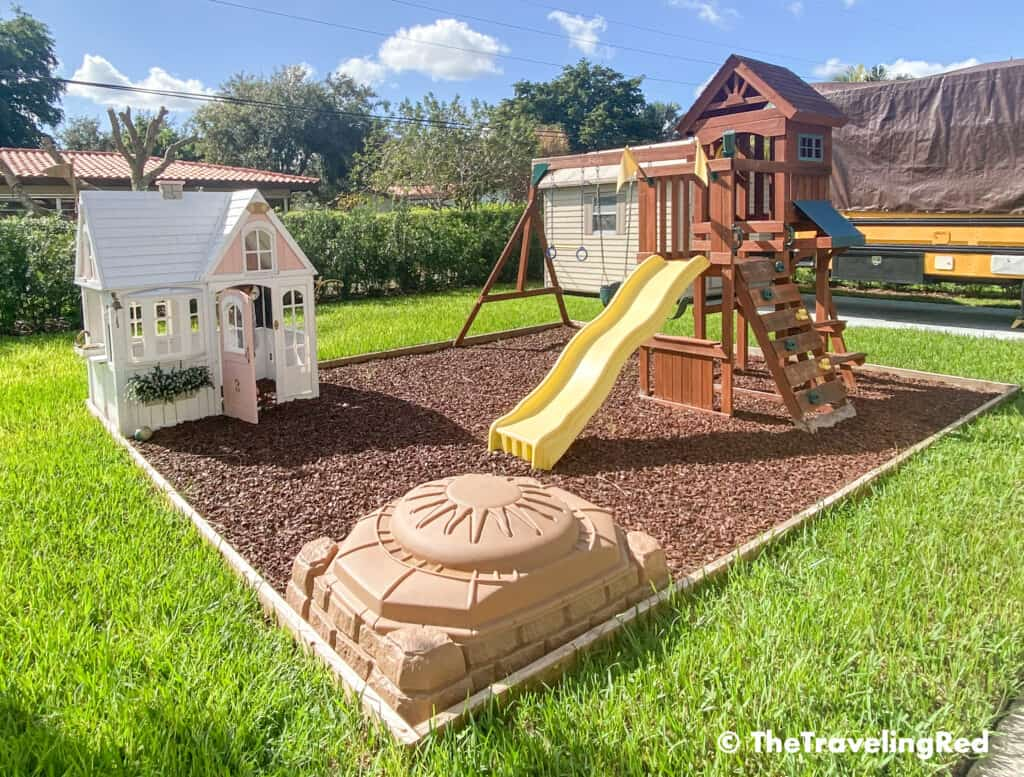 How to build a custom backyard playground with rubber mulch. Our completed space for our swingset, playhouse, sandbox or you can add any other outdoor toys you like. Perfect little outdoor play space for your kids to enjoy playing outside.