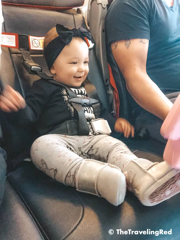 FAA approved airplane harness as an alternative to installing a car seat on an airplane. It it small and fits in your purse. The harness works with the airplane lap belt to restrain similar to a car seat. It does not affect the person sitting behind you because it goes under their tray table.