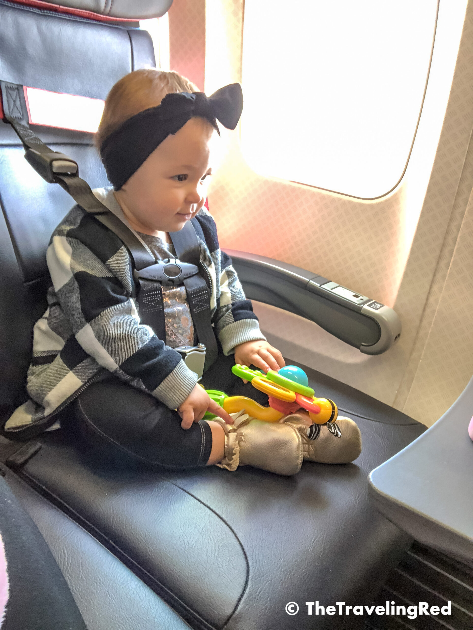 First time using her FAA approved airplane harness. It is an alternative to installing a car seat on an airplane. It it small and fits in your purse. The harness works with the airplane lap belt to restrain similar to a car seat. It does not affect the person sitting behind you because it goes under their tray table.